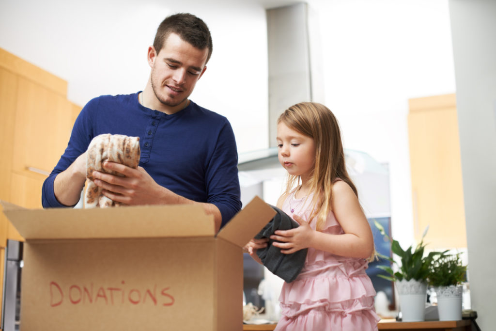 Shot of a father and daughter putting household items into a box for donations.