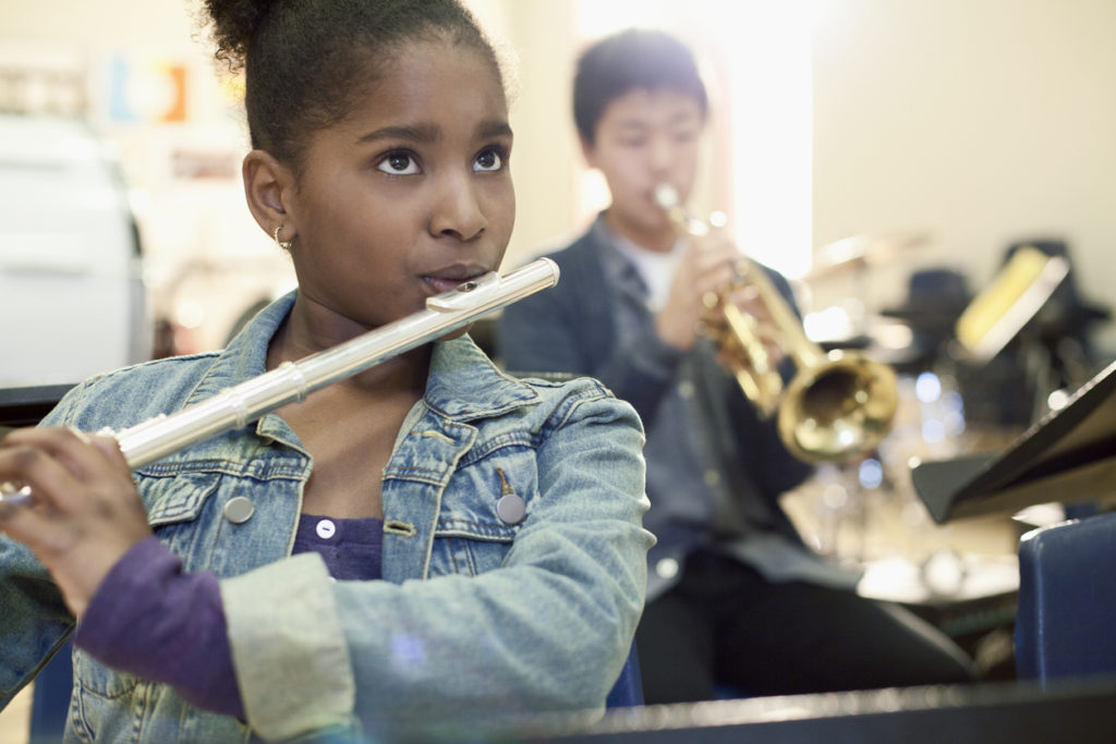 Little girl playing musical instrument in band practice.