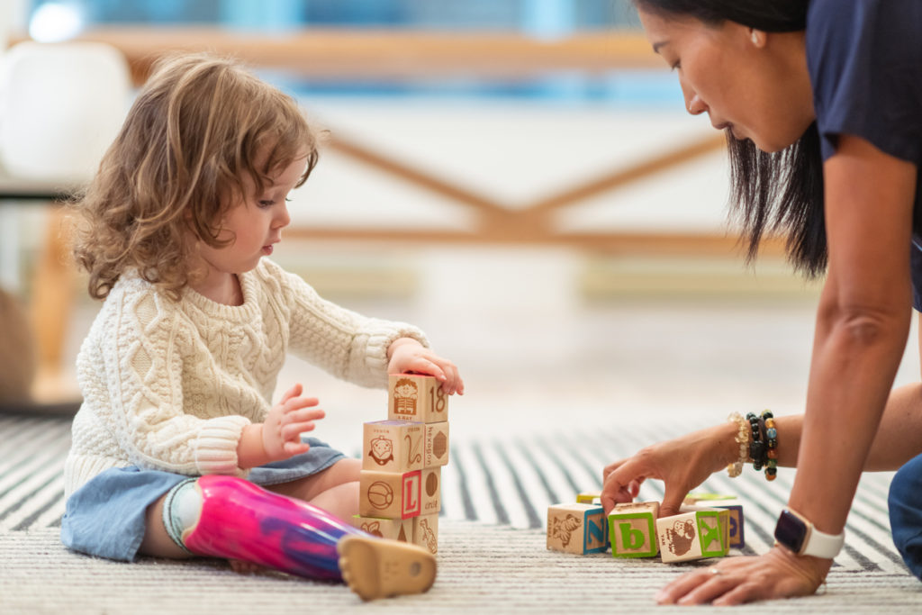 little girl in play therapy with physical therapist